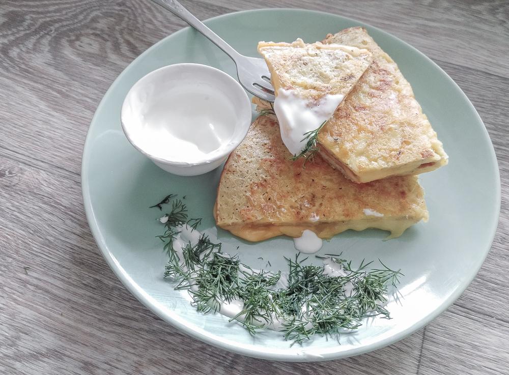 Овсяный блин с сырной корочкой подаём со сметаной и свежим укропом
