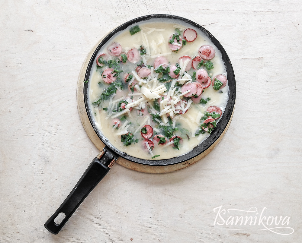 К обжаренным ингредиентам вливаем яйца, равномерно распределяем и посыпаем сыром